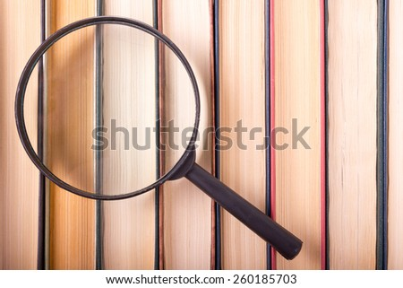 Stack of books with magnifying glass. Search information. - stock photo