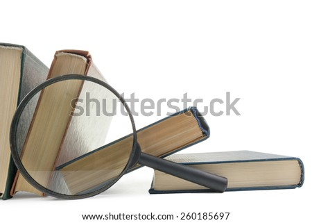 Stack of books with magnifying glass. Search information. Copy space. - stock photo