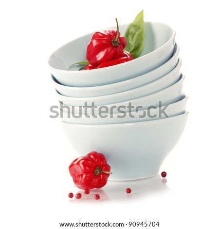Stack of bowls and red peppers over white - stock photo