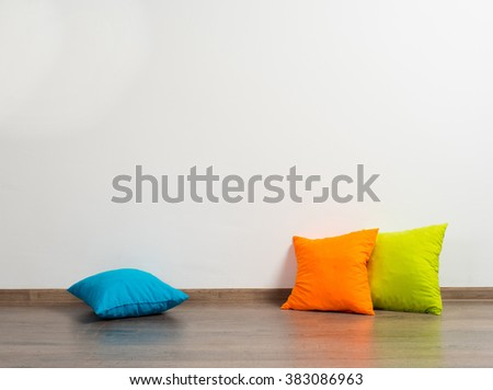 stack of bright pillows on wooden floor - stock photo