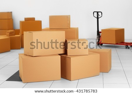 Stack of carton boxes and manual pallet truck indoors - stock photo