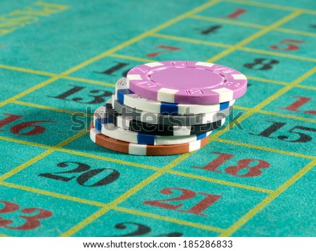Stack of casino chips or tokens on a numbered roulette board in payment of a bet in a gambling game of luck and chance - stock photo