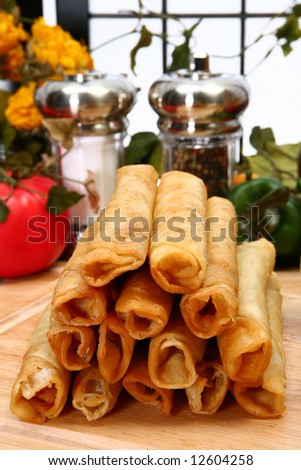 Stack of chicken taquitos with hot sauce and sour cream in kitchen or restaurant - stock photo