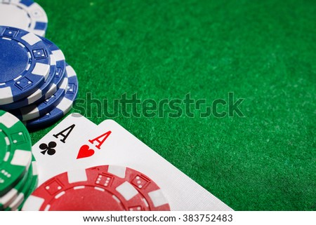 Stack of chips and two aces on the table on the green baize - poker game concept - stock photo
