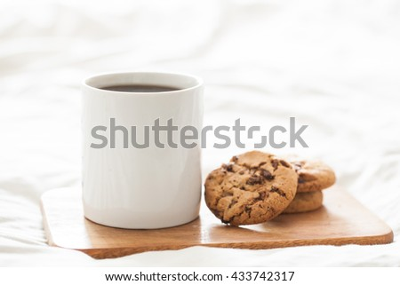 Stack of Chocolate chip cookie and glass of milk in bed. Selective focus. - stock photo