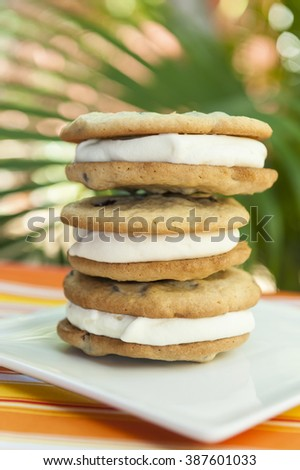 Stack of chocolate chip cookie and vanilla ice cream sandwiches with a tropical background - stock photo