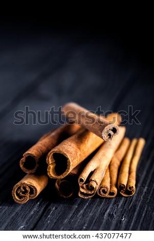 Stack of cinnamon sticks on black wood board. Dark macro photo with selective focus. - stock photo