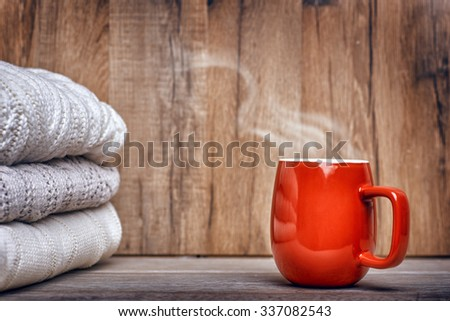 stack of clothes from knitted and cup of drink on a wooden background - stock photo