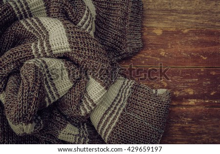 stack of clothes from knitted knitwear on a wooden background / View from the top / Vintage concept / soft focus - stock photo