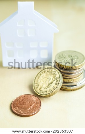 Stack of Coins and home model - stock photo