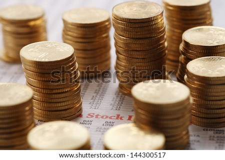 Stack of coins on list of share prices - stock photo