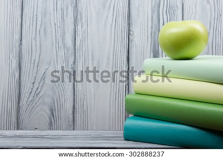 Stack of colorful books and green apple on wooden table. Back to school. Copy space - stock photo