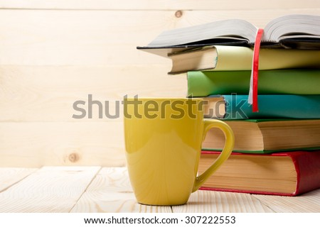 Stack of colorful books, open book and cup on wooden table. Back to school. Copy space - stock photo