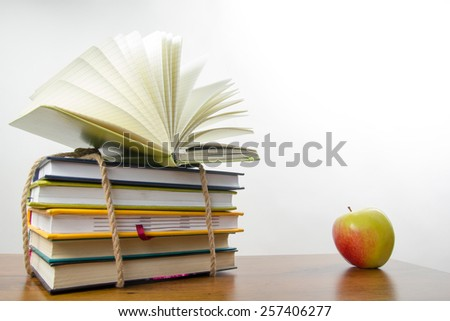 Stack of colorful books tied with a rope and an apple. Back to school. - stock photo