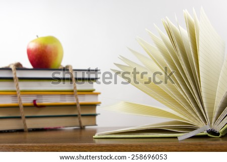 Stack of colorful books tied with a rope, open book and an apple. Back to school on white background. Copy space for text. - stock photo