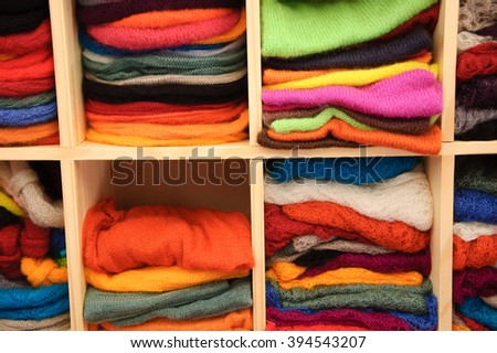 Stack of colorful  knitted colorful clothes - sweaters, dresses, cardigans etc. - stock photo