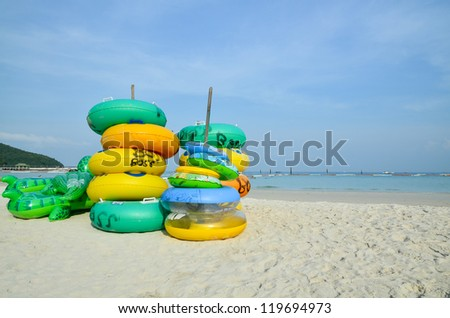 Stack of colorful swimming rings on the beach - stock photo