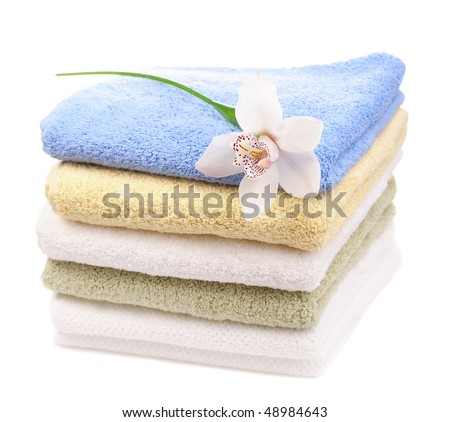 stack of colorful towels with white orchid isolated on white background - stock photo
