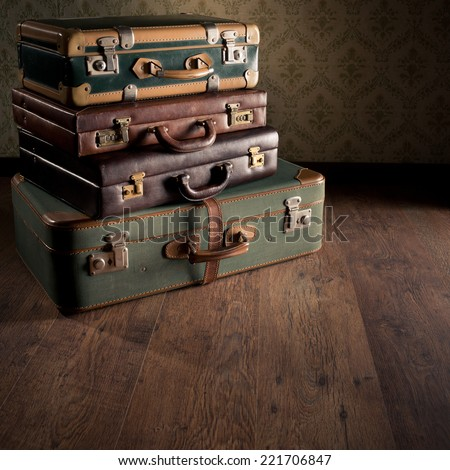 Stack of colorful vintage suitcases on hardwood floor, travelling concept. - stock photo