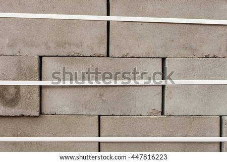 stack of concrete blocks with white packing tape. Grey bricks in a row for the production - stock photo