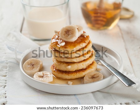 Stack of cottage cheese pancakes with honey and banana, selective focus  - stock photo