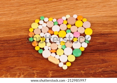 Stack of different pills in the form of a heart on wooden desk - stock photo