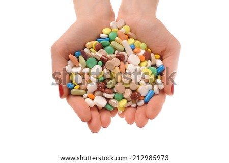 Stack of different pills in the hands over white background  - stock photo