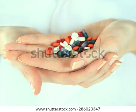 Stack of different pills in woman hands - stock photo