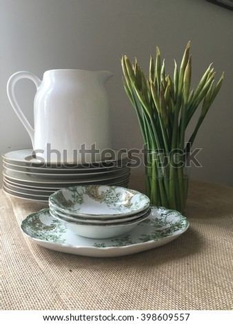 Stack of dishes, a white ceramic water pitcher, daffodils in glass vase, vintage green patterned fruit bowl and platter. - stock photo