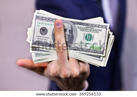 Stack of dollars and  rude gesture - stock photo