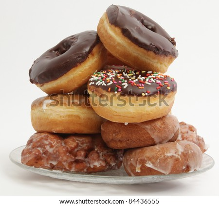 Stack of doughnuts on a plate against white - stock photo