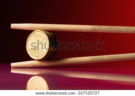 Stack of 20 euro cent coins held by chopstick over red background - stock photo