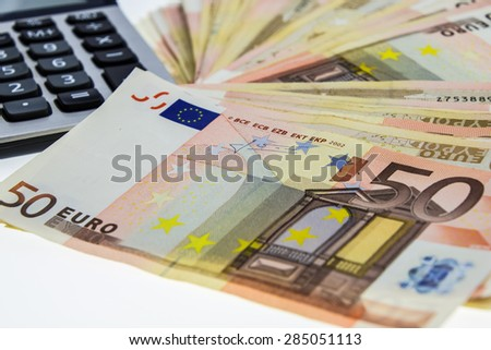 stack of 50 Euro money and calculator - stock photo