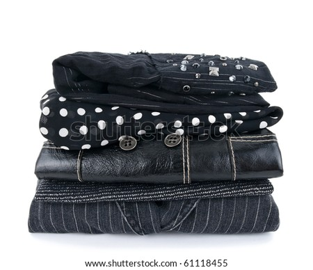 Stack of fashionable black clothes on white background. - stock photo