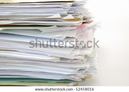 Stack of files full of documents signifying concepts such as work and stress, and business objects. - stock photo