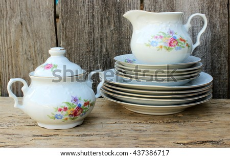 Stack of fine porcelain plates decorated with floral pattern, pot and small jug with old grunge wooden background behind. Vintage kitchen ware in a rustic setting - stock photo