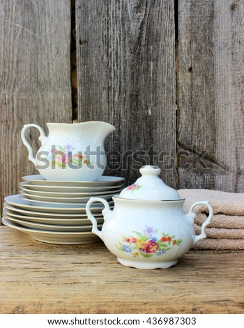 Stack of fine porcelain plates decorated with floral pattern small jug and top with old grunge wooden background behind. Vintage kitchen ware in a rustic setting - stock photo