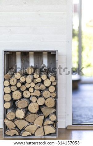 Stack of firewood in modern house - stock photo