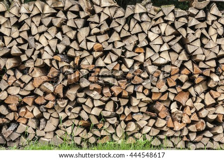 Stack of firewood stapled on a meadow in the Eifel - stock photo