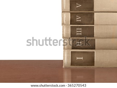 Stack of five old hardcover books on wood table. Brown cloth texture volumes with Roman numerals 1 to 5 on spine. Isolated on white background with copy space.  - stock photo