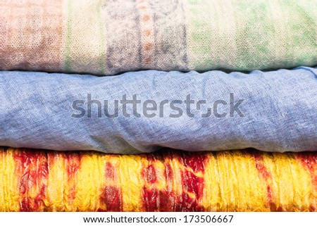Stack of folded colorful asian cloths as a background - stock photo