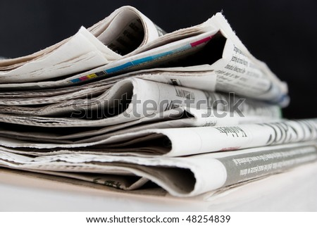 Stack of folded newspapers on black background - stock photo