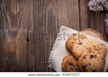 Stack of freshly baked chocolate chip cookies with glass of milk lying on linen napkin on rustic wooden table - stock photo