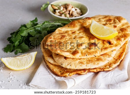 Stack of freshly baked flat bread, lemon and coriander on a table - stock photo