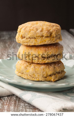 stack of freshly baked homemade pumpkin biscuits on and old barn wood table with a black background - stock photo