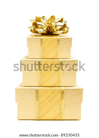 Stack of gold Christmas gift boxes with bow and ribbon over a white background - stock photo