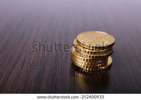 Stack of golden coins on wooden table background - stock photo