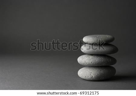 Stack of grey massage stones on dark grey background. - stock photo