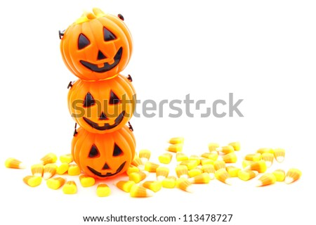 Stack of Halloween jack-o-lantern candy holders with candy corn over white - stock photo