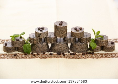 Stack of handmade flavored soap bars with coffee beans and green lavender leafs. - stock photo